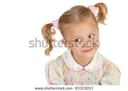 Smiling little girl with two tails wearing a dress on a white background - stock photo