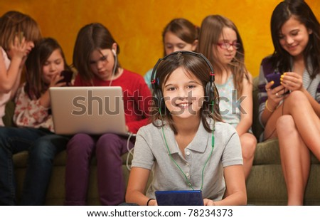 Smiling little girl with video game on a console with friends behind her - stock photo