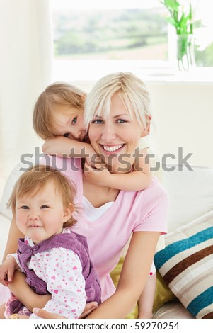 Smiling little girls embracing her mother in the living-room - stock photo