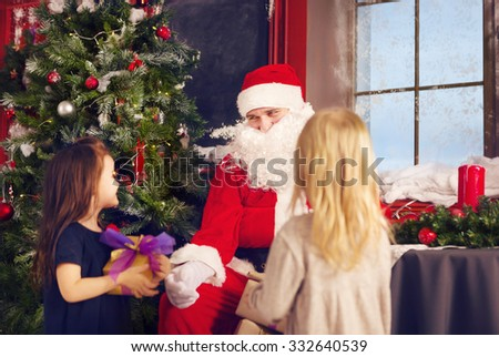 Smiling little girls with Santa Claus and gifts over christmas tree lights background