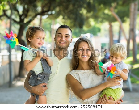 Smiling little girls with windmills sitting on parent's arms outdoor. Focus on woman  - stock photo