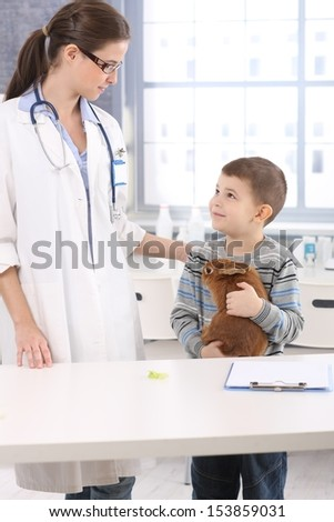 Smiling little kid holding pet rabbit listening to veterinary at pets' clinic. - stock photo