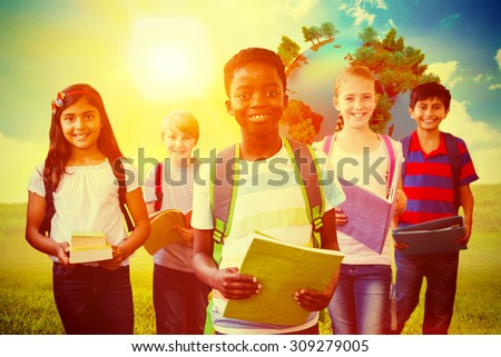 Smiling little school kids in school corridor against blue sky over green field - stock photo