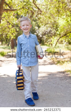 smiling little schoolboy holding book and lunchbag ready to go to school, back to school concept - stock photo
