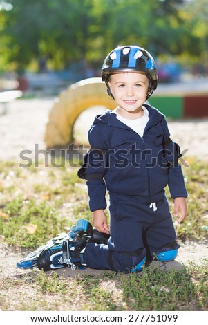 Smiling little skater boy posing on the knee pads - stock photo
