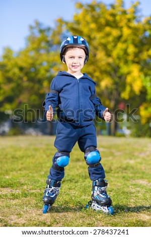 Smiling little skater boy showing two thumb gestures - stock photo