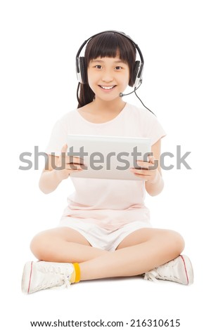 smiling little student girl sitting and holding a tablet with earphone. isolated on white background - stock photo
