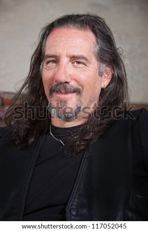 Smiling long haired male with leather vest - stock photo