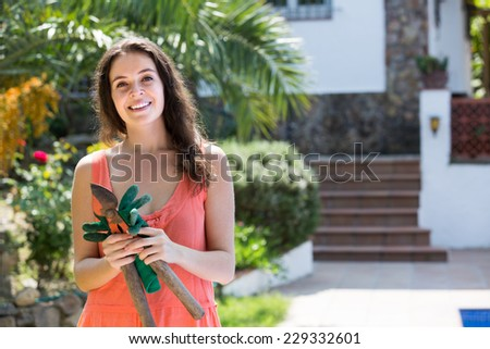 Smiling long-haired woman working with pruning scissors - stock photo