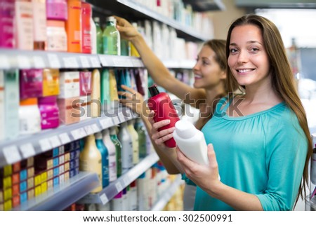 Smiling longhaired brunette girl choosing shampoo at supermarket