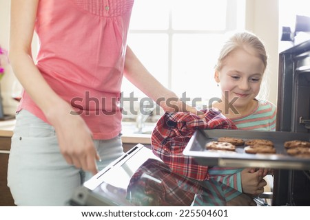 Smiling looking at mother removing cookie tray from oven at home - stock photo