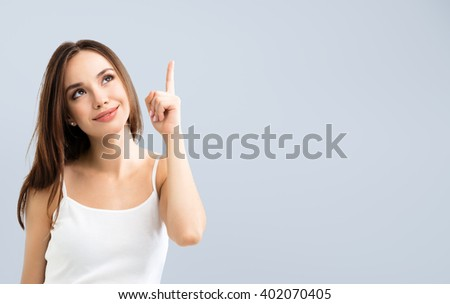 smiling looking up young woman in casual smart clothing, showing something or copyspace for text or slogan, or making idea gesture - stock photo