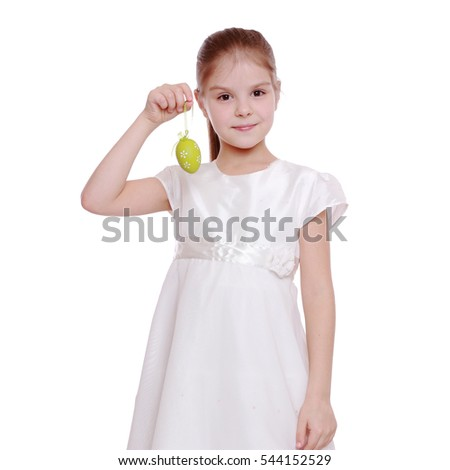 Smiling lovely little girl in holiday dress holding colorful Easter eggs on white background