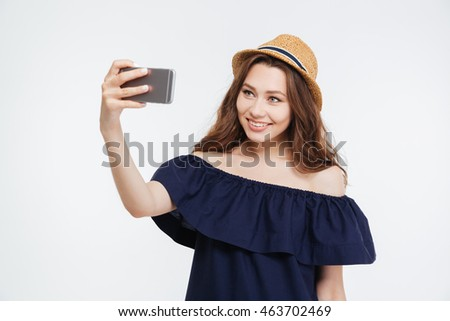 Smiling lovely young woman sending taking selfie with mobile phone over white background
