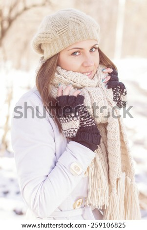 Smiling Lovely Young Woman Winter Portrait at beautiful sunny winter day in the park. Happy Caucasian female wintertime season outdoor. - stock photo