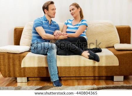 Smiling loving couple sitting on couch