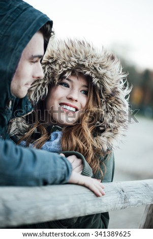 Smiling loving couple with hoods dating during a cold winter day, love and relationships concept - stock photo