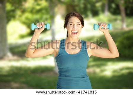 Smiling, luminous young woman lifting small weights in the park - stock photo