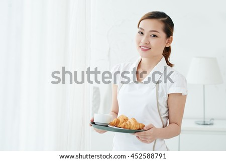 Smiling maid holding tray with breakfast in her hands