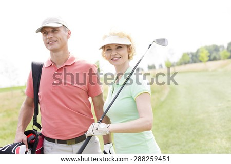 Smiling male and female friends standing at golf course - stock photo