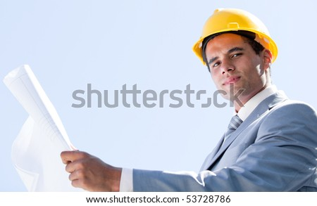 Smiling male architect holding a blueprint outdoor - stock photo