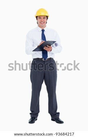 Smiling male architect with pen and clipboard against a white background