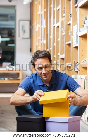 Smiling male customer looking at yellow cardboard box while sitting in shop - stock photo