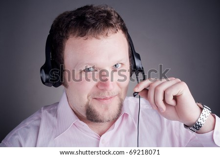 Smiling male customer service operator in headset with grey background