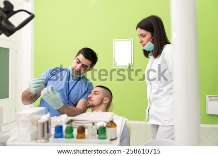 Smiling Male Dentist Explaining Artificial Teeth To Patient In Clinic - stock photo