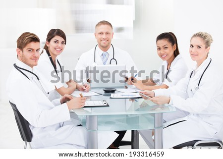 Smiling male doctor discussing with colleagues at desk in clinic - stock photo