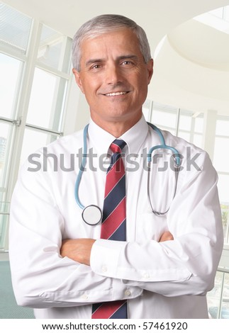 Smiling male doctor in scrubs with a stethoscope around his neck and his arms crossed. Vertical format torso view in modern looking medical facility. - stock photo