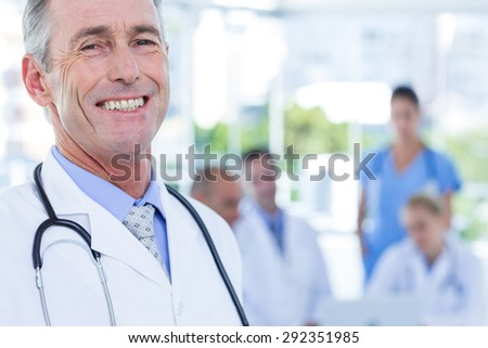 Smiling male doctor looking at camera while his colleagues works in medical office - stock photo