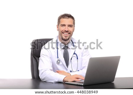 smiling male doctor sitting at table with laptop and stethoscope over white background