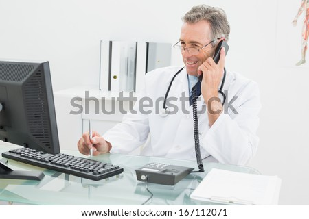 Smiling male doctor using computer and telephone at the medical office - stock photo