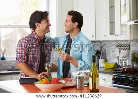 Smiling male gay couple drinking wine while preparing a meal - stock photo