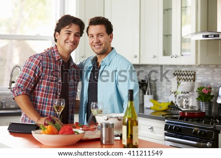 Smiling male gay couple preparing a meal look to camera - stock photo