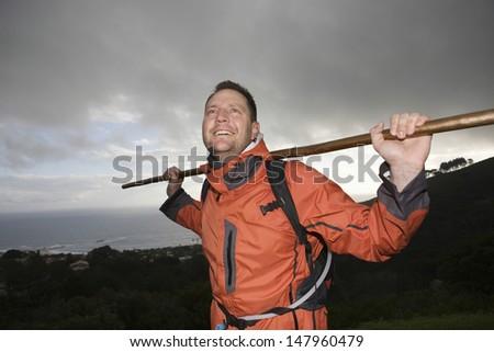 Smiling male hiker holding stick across shoulders on hillside - stock photo