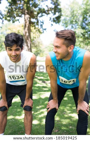 Smiling male marathon runners talking in park - stock photo