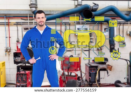 Smiling male mechanic against workshop