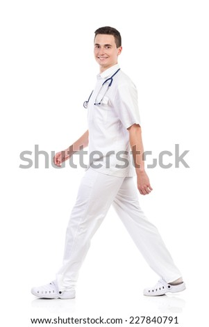 Smiling male nurse walking and looking at camera, side view. Full length studio shot isolated on white. - stock photo