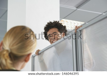Smiling male office worker peering over cubicle wall to greet blond coworker in office - stock photo