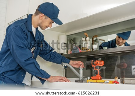 Smiling male person checking water tap