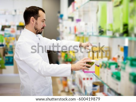 Smiling male pharmacist searching for reliable drug in pharmacy