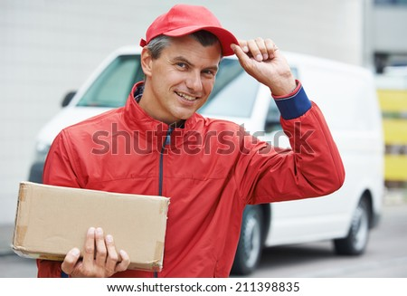 Smiling male postal delivery courier man outdoors  in front of cargo van delivering package - stock photo
