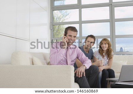 Smiling male real estate agent using mobile phone by couple in new home - stock photo