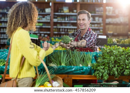 Smiling male staff assisting a woman with grocery shopping in supermarket - stock photo