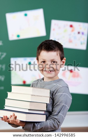 Smiling male student holding a stock of books at the classroom - stock photo