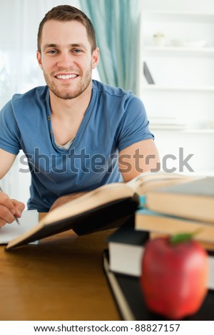Smiling male student with his assignment in front of him