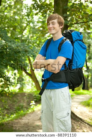 smiling male tourist with backpack on the road - stock photo