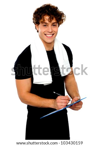 Smiling male trainer writing on clipboard. Towel around his neck - stock photo